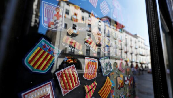 Badges bearing regional flags are sen behind a window reflecting a square in Girona, Spain, October 7, 2017 - Sputnik International