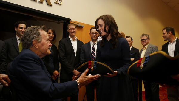 Former President George H.W. Bush, left, receives a tri-corner hat from actress Heather Lind, right, at a private screening of AMC's new series TURN in Houston, Texas. (File) - Sputnik International