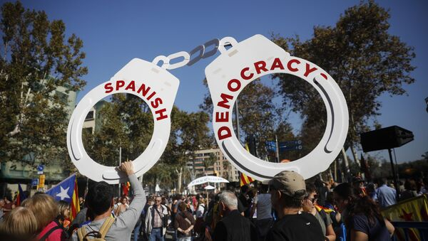 Protesters hold fake handcuffs as they take part a rally outside the Catalan parliament in Barcelona, Spain, Friday, Oct. 27, 2017. - Sputnik International