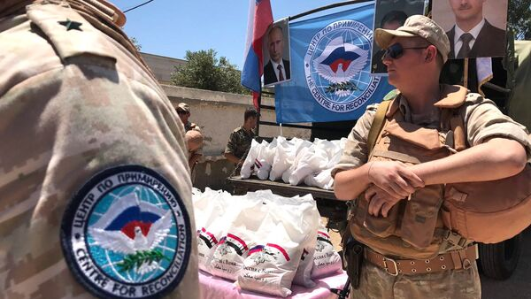 Servicemen of the Russian Center for Reconciliation of Opposing Sides in Syria hand out humanitarian aid in Jiba in the Quneitra province, Syria - Sputnik International