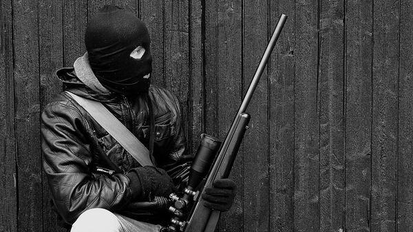 A man wearing a balaclava and holding a weapon - Sputnik International