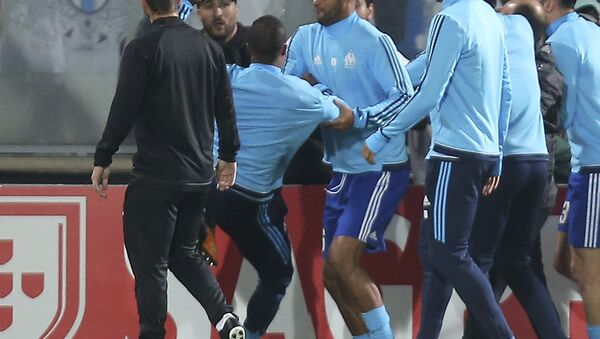 Marseille's Patrice Evra, third left, raises his foot trying to kick a man during a scuffle with Marseille supporters who trespassed into the field before the Europa League group I soccer match between Vitoria SC and Olympique de Marseille at the D. Afonso Henriques stadium in Guimaraes, Portugal, Thursday, Nov. 2, 2017. - Sputnik International
