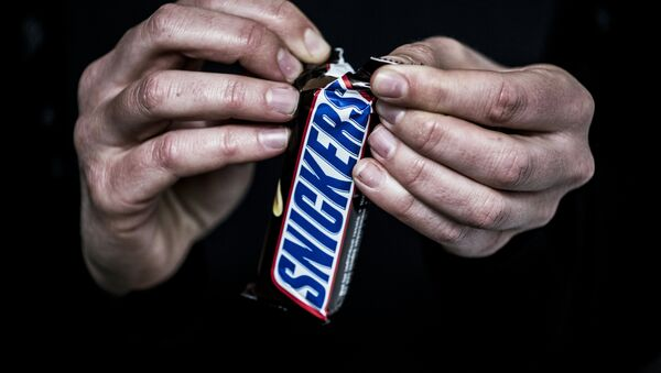 A man opens a Snickers chocolate bar on February 23, 2016 in Lyon, central eastern France - Sputnik International
