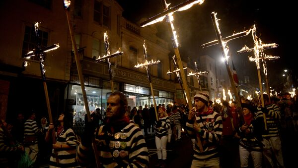 Participants in costumes hold burning crosses as they take part in one of a series of processions during Bonfire Night celebrations in Lewes, Britain November 4, 2017 - Sputnik International