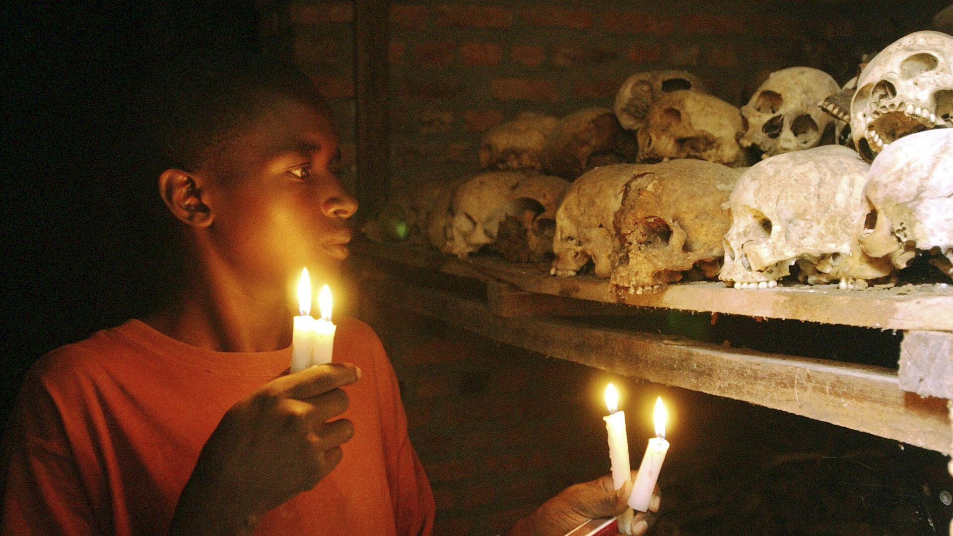 FILE - In this April 6, 2004 file photo, Apollan Odetta, a survivor from the 1994 Rwandan Genocide light candles at a mass grave in Nyamata, Rwanda - Sputnik International, 1920, 20.09.2021