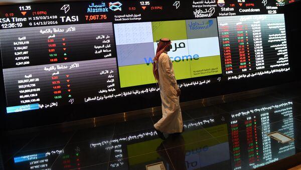 Saudi investor walking past the stock exchange monitors at the Saudi Stock Exchange, or Tadawul, in the capital Riyadh (File) - Sputnik International