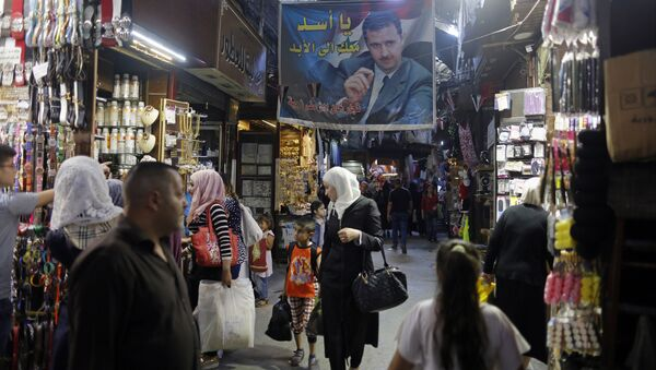 In this May 18, 2017 photo, Syrians shop under a banner showing President Bashar Assad at the Hamadiyah market, in the Old City of Damascus, Syria. - Sputnik International