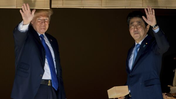 President Donald Trump and Japanese Prime Minister Shinzo Abe wave to members of the media after feeding fish at a koi pond at the Akasaka Palace, Monday, Nov. 6, 2017, in Tokyo. - Sputnik International