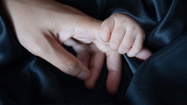An adult holding a baby's hand - Sputnik International