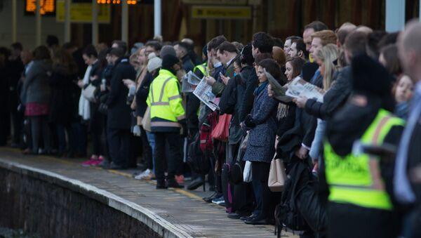 Commuters wait on a platform to catch a train toward central London - Sputnik International