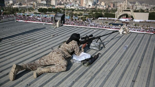A Houthi Shiite sniper keeps watch over a rally to mark the third anniversary of the Houthis' takeover of the Yemeni capital, in Sanaa. - Sputnik International