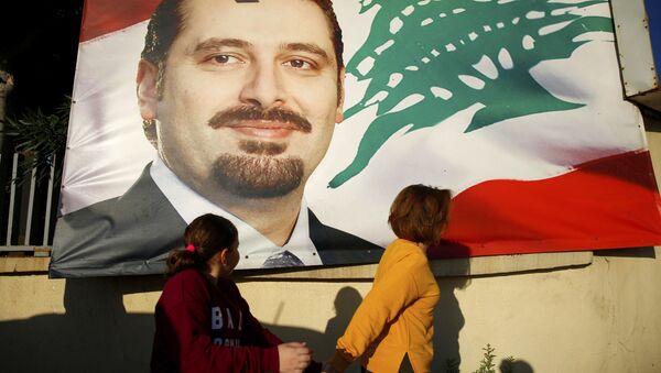 A woman and her daughter pass by a poster of outgoing Prime Minister Saad Hariri, in Beirut, Lebanon, Saturday, Nov. 11, 2017. Lebanon's president has called on Saudi Arabia to clarify the reasons why the country's prime minister has not returned home since his resignation which was announced from the kingdom - Sputnik International