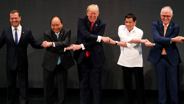 U.S. President Donald Trump smiles with other leaders, including Russia's Prime Minister Dmitry Medvedev, Vietnam's Prime Minister Nguyen Xuan Phuc, President of the Philippines Rodrigo Duterte and Australia's Prime Minister Malcolm Turnbull, as they cross their arms for the traditional ASEAN handshake in the opening ceremony of the ASEAN Summit in Manila, Philippines November 13, 2017 - Sputnik International