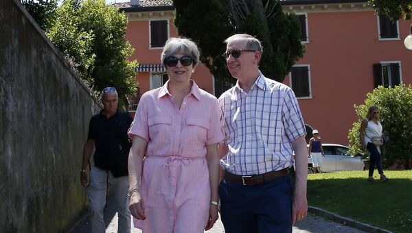 Britain Prime Minister Theresa May, left, walks with her husband Philip as they visit Desenzano del Garda, by the Garda lake, northern Italy, Tuesday, July 25, 2017. May is spending her holidays in northern Italy. - Sputnik International