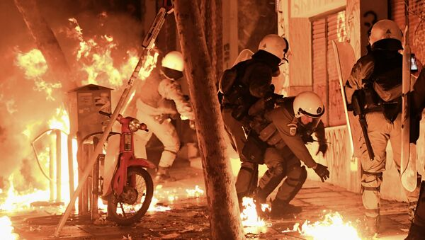 A petrol bomb explodes next to anti-riot policemen in downtown Athens on November 17, 2017, during clashes following a rally commemorating the 1973 students uprising against the US-backed military junta - Sputnik International
