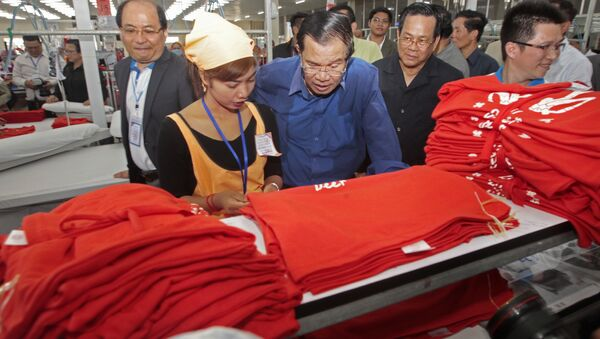 Cambodian Prime Minister Hun Sen, center, leans over a garment worker - Sputnik International