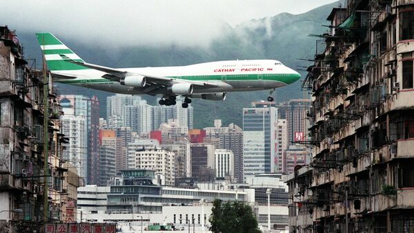 Hong Kong flag carrier Cathay Pacific, Boeing 747-400 jumbo jet, flies over the Kai Tak Airport control tower bottom as it approaches the Runway 13 on the last day of the 73-year-old airport - Sputnik International