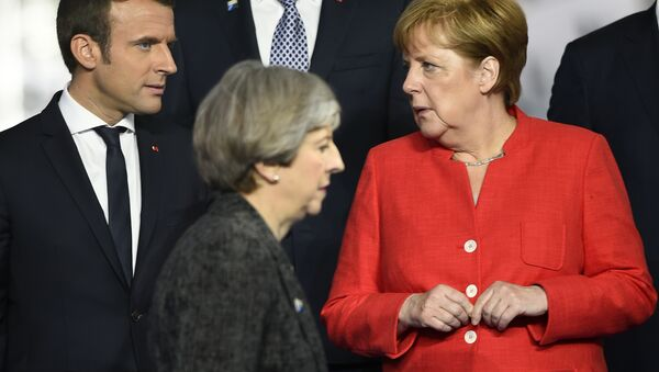 Britain's Prime Minister Theresa May, foreground walks by French President Emmanuel Macron, left, and German Chancellor Angela Merkel as they gather with NATO member leaders to pose for a group photo, prior to the start of their summit in Brussels, Belgium, Thursday, May 25, 2017. - Sputnik International