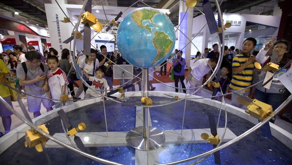 Visitors look at a mockup of China's homegrown Beidou satellite navigation system at the China Beijing International High-Tech Expo in Beijing, Saturday, June 10, 2017 - Sputnik International