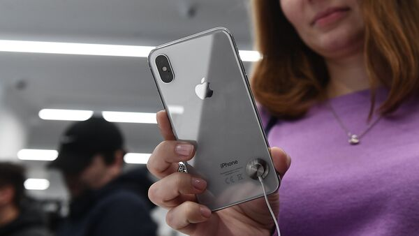 A buyer examines a new smartphone iPhone X in re:Store mobile equipment store on Tverskaya Street in Moscow - Sputnik International