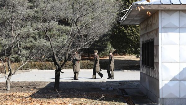 Three North Korean soldiers look at the South side at the spot where a North Korean soldier crossed the border at the Panmunjom in the Demilitarized Zone, South Korea - Sputnik International