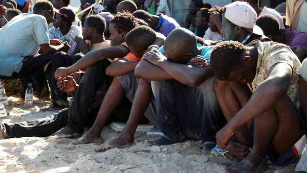 Illegal migrants from sub-Saharan Africa rest after they were rescued by the Libyan coast guard when their boat sank off the coastal town of Guarabouli, 60 km (36 miles) east of the capital Tripoli on October 2, 2014 - Sputnik International