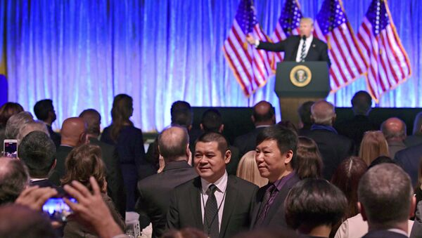 People in the audience have their photo taken as President Donald Trump speaks at a fundraiser - Sputnik International
