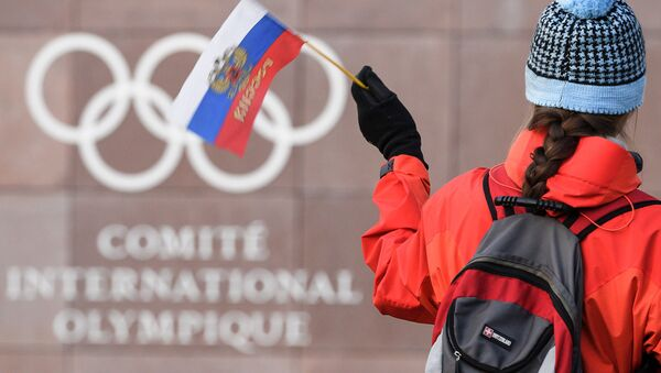 A supporter waves a Russian flag in front of the logo of the International Olympic Committee (IOC) at their headquarters on December 5, 2017 in Pully near Lausanne - Sputnik International