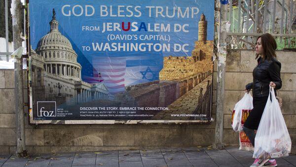 A woman walks past a poster praising U.S. President Donald Trump's recognition of Jerusalem as Israel's capital, in Jerusalem, Thursday, Dec. 7, 2017 - Sputnik International