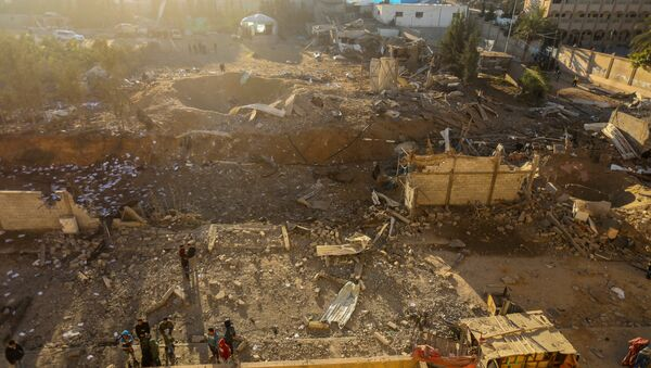 Palestinians look at the damage at a Hamas military facility early on December 9, 2017, in the aftermath of an Israeli air strike in Beit Lahia, in the northern Gaza Strip - Sputnik International