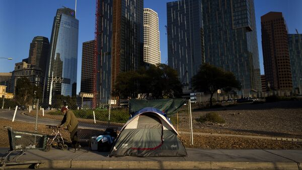 A homeless man, who declined to give his name, is dwarfed by skyscrapers Monday, Dec. 4, 2017, in Los Angeles. The U.S. Department on Housing and Urban Development release of the 2017 homeless numbers are expected to show a dramatic increase in the number of people lacking shelter along the West Coast. - Sputnik International
