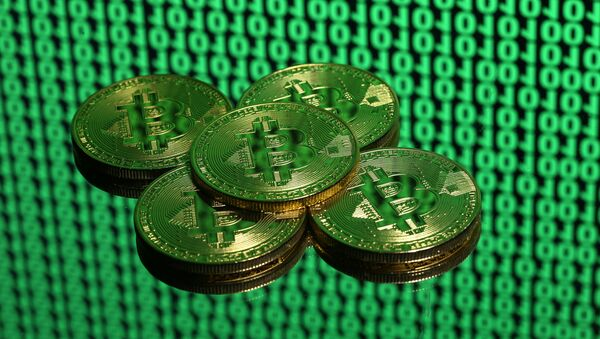Tokens of the virtual currency Bitcoin are seen placed on a monitor that displays binary digits in this illustration picture, December 8, 2017 - Sputnik International