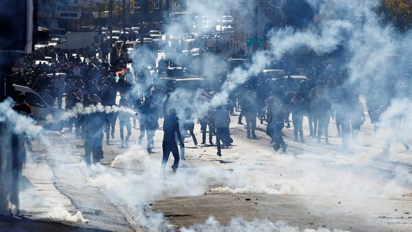 Palestinian demonstrators react to tear gas fired by Israeli troops during clashes at a protest against U.S. President Donald Trump's decision to recognize Jerusalem as the capital of Israel, in the West Bank city of Bethlehem December 9, 2017 - Sputnik International