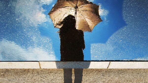 A silhouette of a woman holding an umbrella - Sputnik International