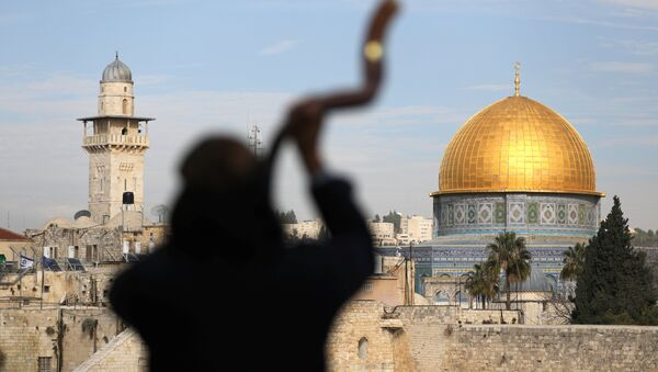 A man is silhouetted while he blows a Shofar, a ram horn, as the Dome of the Rock (R), located in Jerusalem's Old City on the compound known to Muslims as Noble Sanctuary and to Jews as Temple Mount, is seen in the background December 10, 2017 - Sputnik International