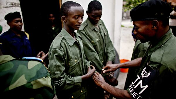 (File) A Congolese solider places handcuffs on Shumbushu Eric, a soldier accused of rape and crimes against humanity, outside his holding cell in the town of Baraka on Thursday, Feb. 17, 2011 - Sputnik International