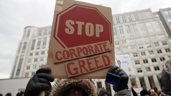 A woman hold a sign that reads Stop Corporate Greed during a protest at the Federal Communications Commission (FCC), in Washington, Thursday, Dec. 14, 2017 - Sputnik International