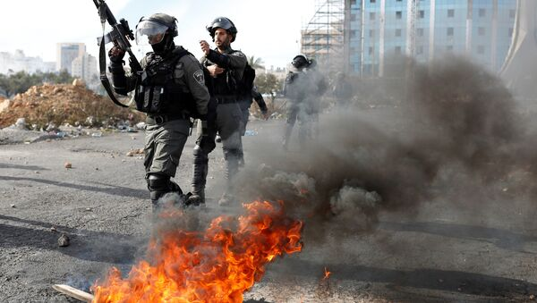 Israeli police officers walk in front of a burned barricade during a protest against U.S. President Donald Trump's decision to recognize Jerusalem as the capital of Israel, near the Jewish settlement of Beit El, near the West Bank city of Ramallah December 11, 2017 - Sputnik International