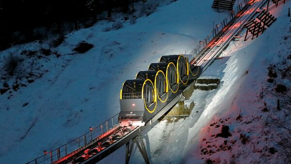 The barrel-shaped carriages of a new funicular line are seen on the illuminated track before the opening ceremony near the Alpine resort of Stoos, Switzerland December 15, 2017 - Sputnik International