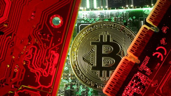 A coin representing the bitcoin cryptocurrency is seen on computer circuit boards in this illustration picture, October 26, 2017 - Sputnik International