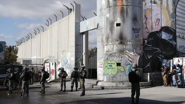 Israeli forces stand near the controversial separation barrier bearing graffiti depecting US President Donald Trump during clashes with Palestinian protestors near an Israeli checkpoint in the West Bank city of Bethlehem on December 7, 2017 - Sputnik International