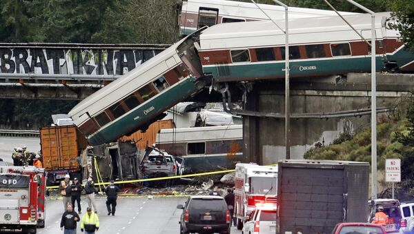 Cars from an Amtrak train lay spilled onto Interstate 5 below alongside smashed vehicles as some train cars remain on the tracks above Monday, Dec. 18, 2017, in DuPont, Wash. The Amtrak train making the first-ever run along a faster new route hurtled off the overpass Monday near Tacoma and spilled some of its cars onto the highway below, killing some people, authorities said. Seventy-eight passengers and five crew members were aboard when the train moving at more than 80 mph derailed about 40 miles south of Seattle before 8 a.m., Amtrak said. - Sputnik International