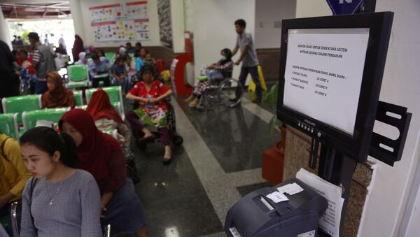 Patients wait near a queue number dispenser affected by WannaCry attack at Dharmais Cancer Hospital in Jakarta, Indonesia, Monday, May 15, 2017 - Sputnik International