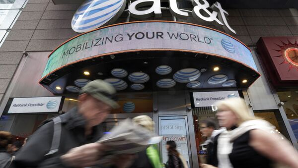 In this Oct. 21, 2014 photo, people pass an AT&T store in New York's Times Square. AT&T is being sued by the government over allegations it misled millions of smartphone customers who were promised unlimited data but had their Internet speeds cut by the company — slowing their ability to open web pages or watch streaming video. - Sputnik International
