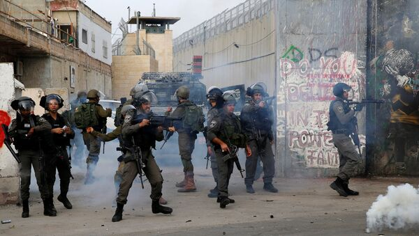 An Israeli border policeman fires tear gas canisters at Palestinian demonstrators during clashes in the West Bank city of Bethlehem, December 23, 2017 - Sputnik International