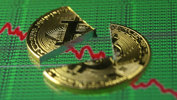 Broken representation of the Bitcoin virtual currency, placed on a monitor that displays stock graph and binary codes, are seen in this illustration picture, December 21, 2017 - Sputnik International