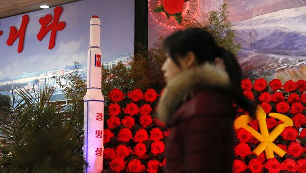 In this Feb. 15, 2016 file photo, a visitor at a flower festival walks past a model of North Korea's newest satellite Kwangmyongsong 4 on display - Sputnik International
