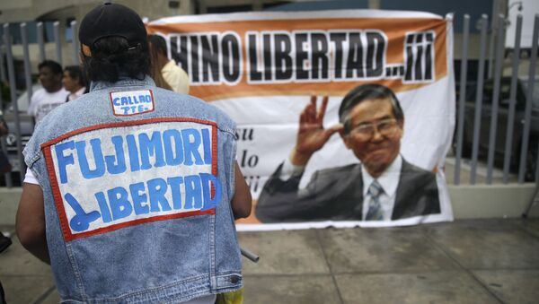 A supporter of former President Alberto Fujimori wears a jacket that says in Spanish Free Fujimori outside the clinic where the jailed leader was admitted the previous day after suffering a drop in blood pressure in Lima, Peru, Sunday, Dec. 24, 2017. The former strongman, who governed from 1990 to 2000, is a polarizing figure in Peru. Some Peruvians laud him for defeating the Maoist Shining Path guerrillas, while others loathe him for human rights violations carried out under his government. (AP Photo/Martin Mejia) - Sputnik International