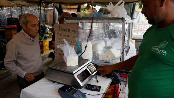 A vendor weighs cheese for a customer at a street market in Caracas, Venezuela December 19, 2017. Picture taken December 19, 2017. - Sputnik International
