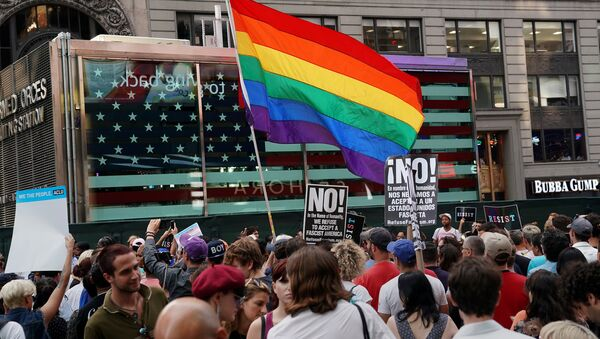 A rainbow flag flies as people protest U.S. President Donald Trump's announcement that he plans to reinstate a ban on transgender individuals from serving in any capacity in the U.S. military, in Times Square, in New York City, New York, U.S., July 26, 2017. - Sputnik International